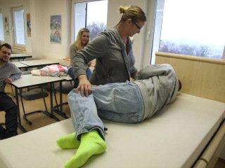 Anni Richarz zeigt, wie man jemanden im Pflegebett dreht. Foto: SMMP/Hofbauer